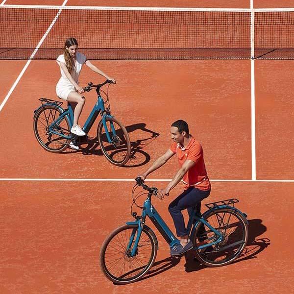 Un homme et une femme et leur vélo électrique sur un terrain de Roland Garros