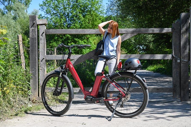 Une femme au près de son vélo électrique dans un chemin de terre