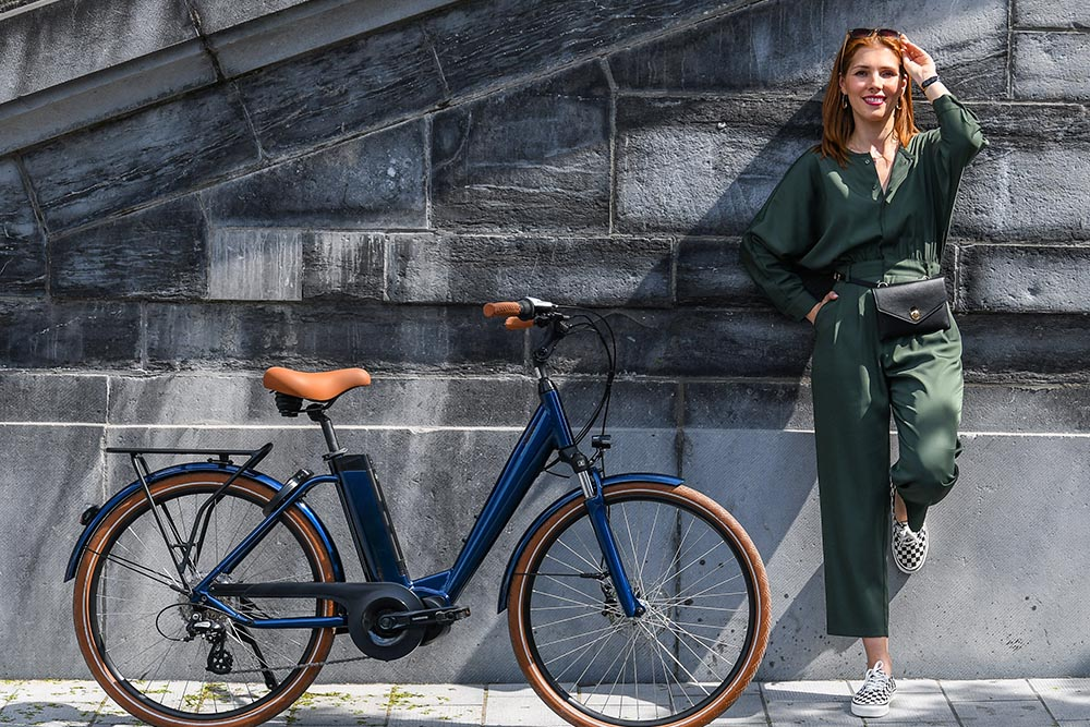 Une femme adossée à un mur à côté de son vélo électrique