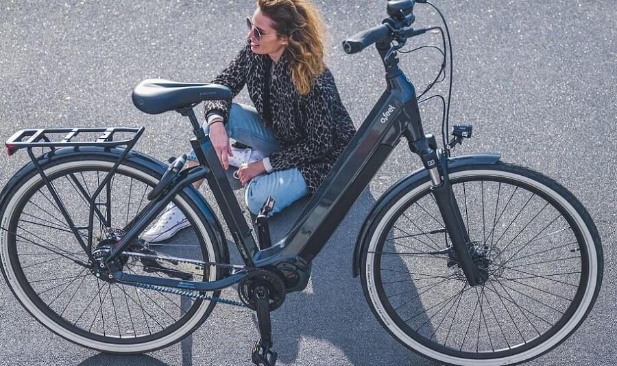 Une femme assise à côté de son vélo électrique
