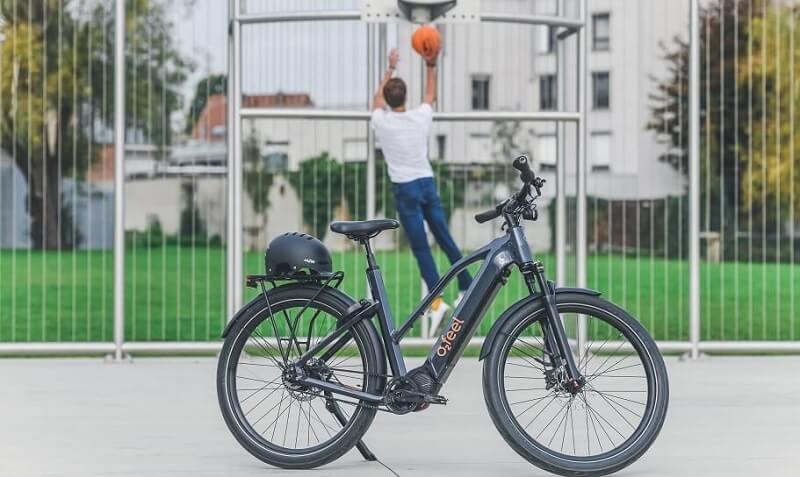 Un homme jouant au basket à côté de son vélo électrique