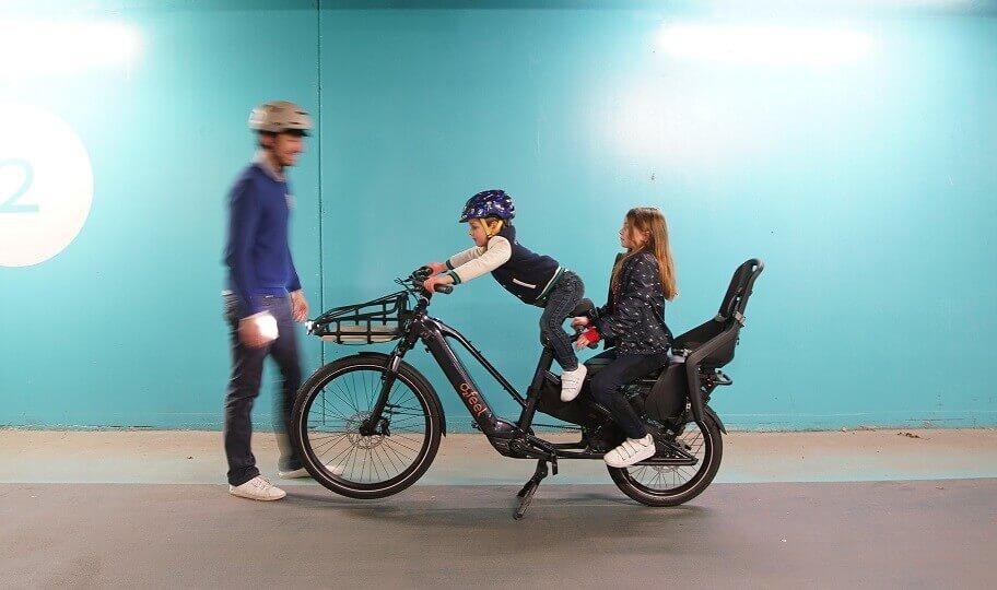 Un père et ses deux enfants avec un vélo électrique cargo