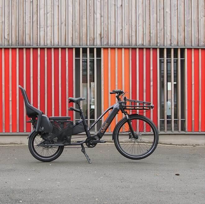 Un vélo électrique cargo garé devant un bâtiment